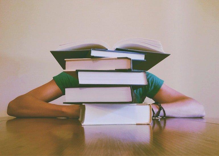 ragazza appoggiata alla scrivania nascosta da una pila di libri
