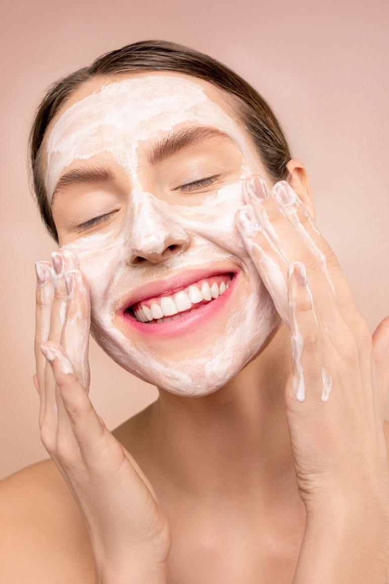 donna che lava il viso con un detergente