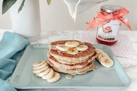 pancakes integrali serviti su vassoio con banana a fette e miele