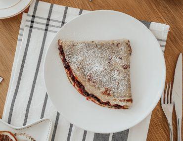 crepes con farina di avena servita su un piatto bianco con marmellata di frutti di bosco